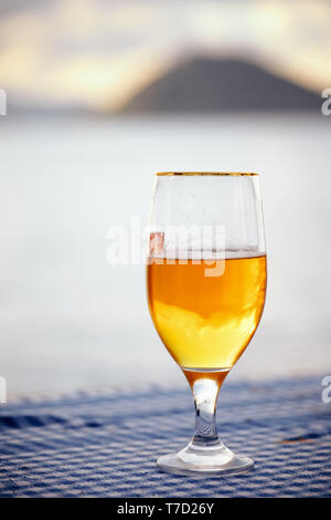 Half full glass of  beer on the table with blurred sea, sky and island background at sunset. - Stock Image