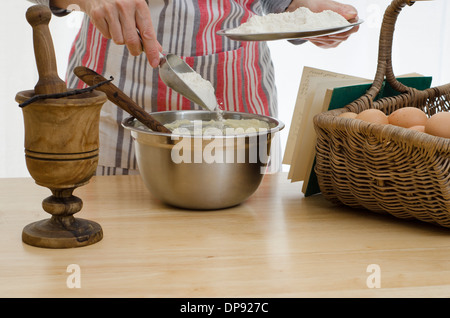 Woman baking a cake, adding flour to a bowl, surrounded by the other ingredients and a recipe book - Stock Image