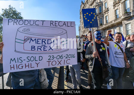 London, UK. 20th October 2018. A woman holds a 'Product Recall' poster for Farage's 'Merde de Brex' at the side of the People's Vote March calling for a vote to give the final say on the Brexit deal or failure to get a deal as the march leaves Hyde Park Corner. They say the new evidence which has come out since the referendum makes it essential to get a new mandate from the people to leave the EU. Peter Marshall/Alamy Live News - Stock Image