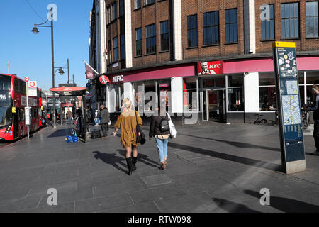 Rear view of women walking past KFC Kentucky Fried Chicken restaurant on Brixton Road in Brixton, Borough of Lambeth, South London UK   KATHY DEWITT - Stock Image