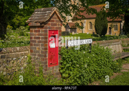 A traditional red post box by the churchyard in the village of Fingest, Buckinghamshire - Stock Image