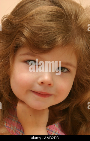 Portrait of young girl with cheeky grin - Stock Image