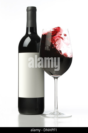 A bottle of red wine with a splashing glass of red wine. - Stock Image