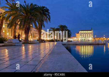 Waterfront of Split Croatia just after sunset. Lit buildings and palm trees, with reflection in water - Stock Image