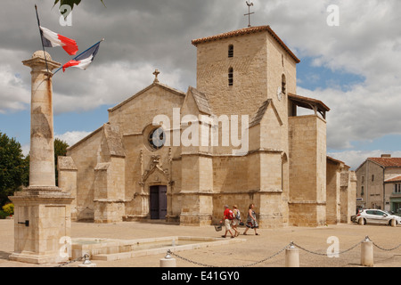 French church in Coulon with tricolor flying outside. - Stock Image