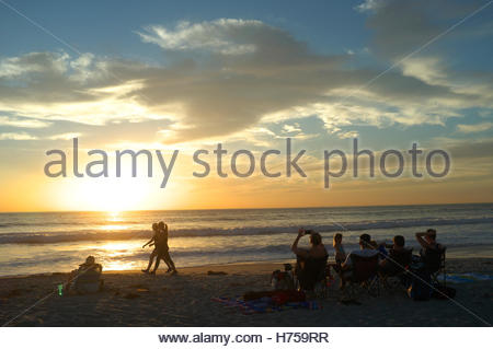 Watching the sun set across the Pacific Ocean, at Solana Beach (San Diego), California, USA. - Stock Image