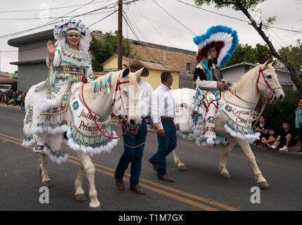 Teens costumed as Princess Pocahontas and Chief White Eagle ride white horses in the Washington's Birthday Celebration parade in Laredo, TX. - Stock Image