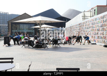 Fitness group in front of exhibition of Face magazine covers on side of Lewis Cubitt Square at CDY, Kings Cross, London, UK - Stock Image