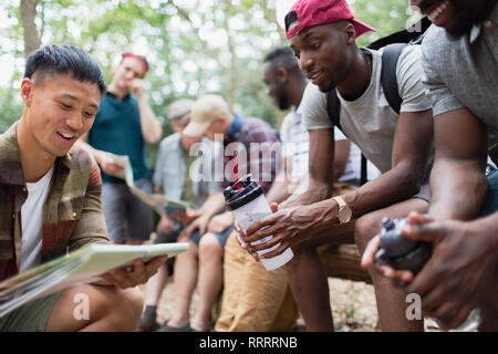 Men friends looking at hiking map in woods - Stock Image