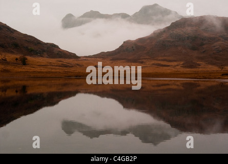 Blea Tarn with the Langdale Pikes shrouded in mist in autumn - Stock Image