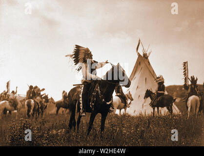 Edward S. Curits Native American Indians -  Dakota man, wearing war bonnet, sitting on horseback, his left hand outstreched toward tipi  ca. 1907 - Stock Image