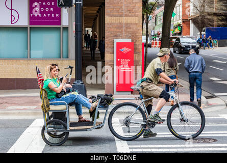 CHARLOTTE, NC, USA-3/16/19: Two young women look at smart phones while riding in a bicycle towed cart in uptown Charlotte. - Stock Image