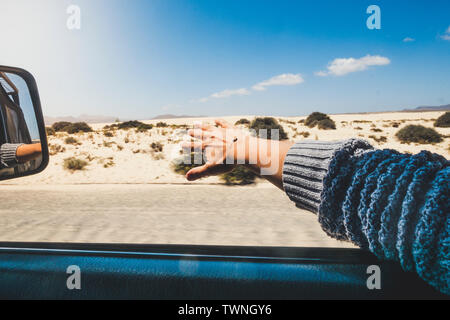 People traveling by car and summer holiday vacation concept - woman's hand play with the wind outside the window of the vehicle while drive on a road - Stock Image