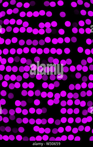 Unfocused abstract violet bokeh on black background. defocused and blurred many round light. - Stock Image
