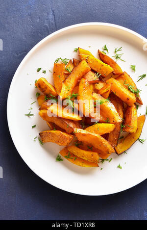 Roasted pumpkin slices on white plate over blue stone background. Healthy vegetarian, vegan food. Top view, flat lay - Stock Image