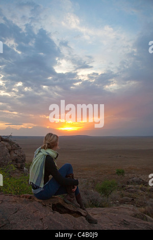 Tanzania, Olduvai. A tourist enjoys the sunset looking out over the plains towards the Serengeti. MR. - Stock Image