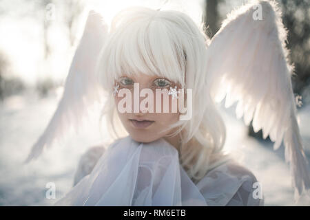 Portrait of beautiful blonde girl in image of good angel with wings dressed in white clothing. - Stock Image