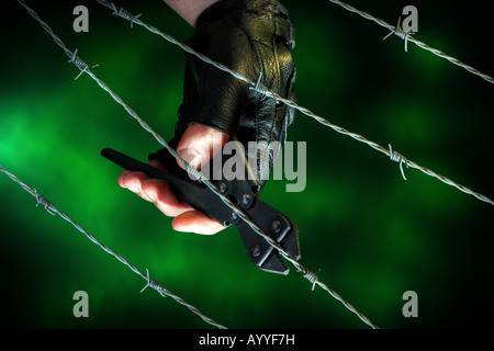 Barb wire being cut - Stock Image