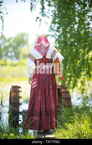 Young woman in traditional russian clothes stands on a small bridge near the lake, with a balalaika behind her back, backview - Stock Image