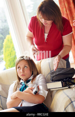 mother telling her teenage daughter to do her homework - Stock Image
