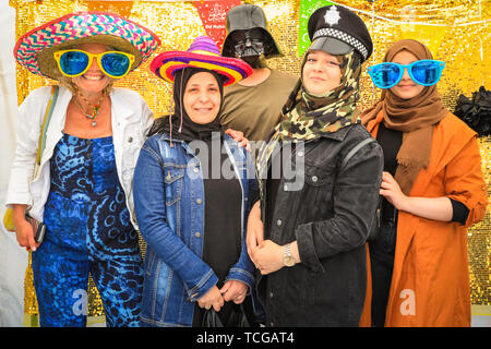 Trafalgar Square, London, UK, 08th June 2019. People have fun being photographed in the 'hats of faith photo booth' for Eid. Thousands of Londoners and visitors come together on Trafalgar Square to celebrate the end of Ramadan and Eid Festival, as well as London's rich cultural diversity. The festival is hosted by Mayor of London Sadiq Khan. - Stock Image