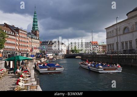 Canal tour boats and view towards Nikolaj Kirke from Gammel Strand, Copenhagen, Denmark - Stock Image