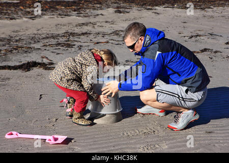 Father and daughter making sandcastles on the beach, Isle of Mull, Scotland - Stock Image