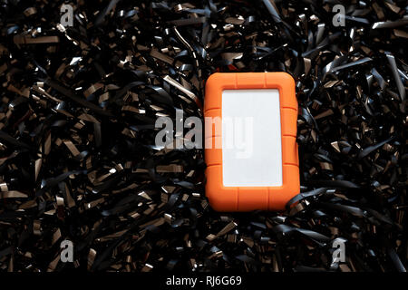 LaCie Portable storage device, no logo, on a bed of magnetic tape. - Stock Image