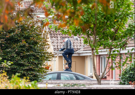 Macroom, West Cork, Ireland. 8th Oct, 2018. A Garda searches a roof opposite the home of the murder victim who has been named locally as 44 year old Timmy Foley. Credit: Andy Gibson/Alamy Live News. - Stock Image