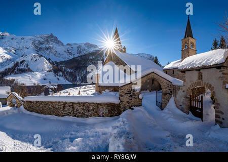 La Grave, Hautes-Alpes, Ecrins National Park, Alps, France: The local village of La Grave and its church with La Meije mountain peak in winter - Stock Image