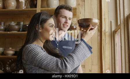 Low angle view of boyfriend and girlfriend admiring handmade ceramic bowl in store - Stock Image