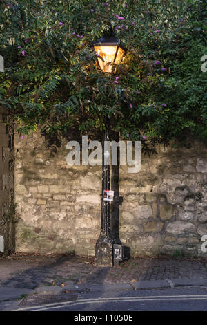 Oxford, UK. Old gas streetlight converted to electricity, in medieval Longwall Street beside Magdalen College - Stock Image