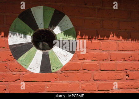 Window in a Danish red brick barn: Detail of the wall of an old barn in the Lyngby Folk museum.  A round window decorated with green, white and black paint shaded by the thatched roof. - Stock Image