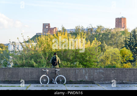 Man in Vilnius, Lithuania, with a fixed-gear bicycle, in fromt of Gediminas hill - Stock Image