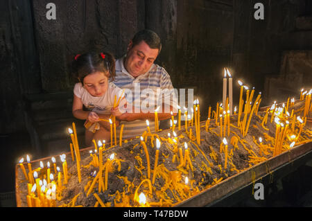 Armenia, Goght, people lighting prayer candles in rock-cut chamber of Geghard Monastery, founded 4th c by Gregory the Illuminator at the site of a sac - Stock Image