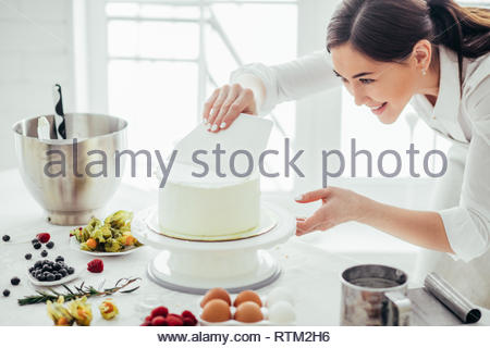 cheerful girl using a smooother while baking cake in the kitchen. close up photo. - Stock Image
