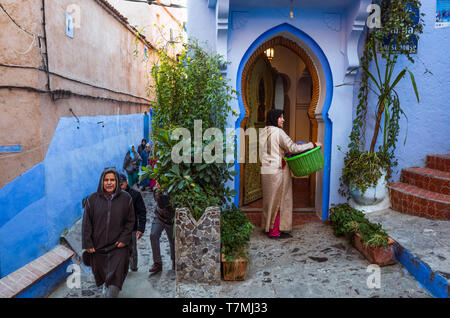 Chefchaouen, Morocco : Moroccan men walk past a blue-washed door in the alleyways of the medina old town. - Stock Image