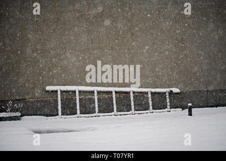 Old wooden ladder laying on the snow near the wall. - Stock Image