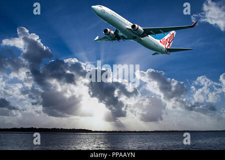 Sydney, New South Wales, Australia - February 27. 2015: Virgin Airlines commercial passenger jet aircraft in flight departing Sydney. - Stock Image