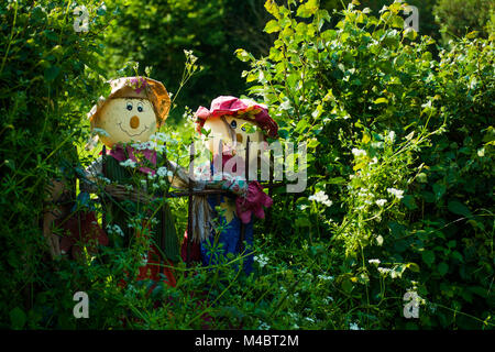 Two funny rag dolls looking over a fence in a gap in the hedgerow along a country lane in Buckinghamshire, England - Stock Image