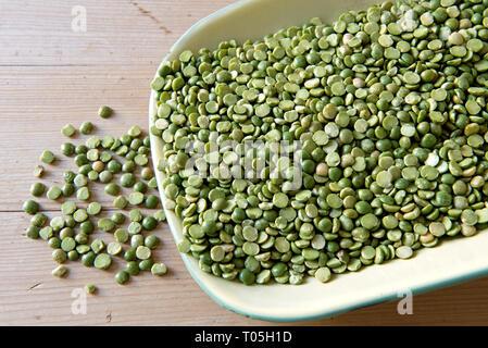 Split Green Peas slilt out of vintage green enamel dish on kitchen table - Stock Image