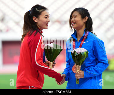Doha, Qatar. 23rd Apr, 2019. Lu Minjia(L) of China shakes hands with Yue Ya Xin of Chinese Hong Kong during the victory ceremony of the women's long jump final during 23rd Asian Athletics Championships at Khalifa International Stadium in in Doha, capital of Qatar, April 23, 2019. (Xinhua/Wu Huiwo) Credit: Wu Huiwo/Xinhua/Alamy Live News - Stock Image
