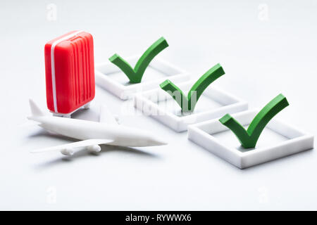 Miniature Red Bag And Plane With Checklist On White Backdrop - Stock Image