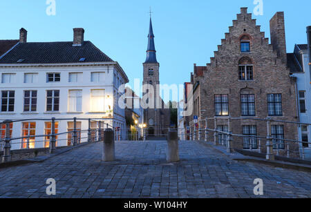 Scenic city view of Bruges with beautiful medieval houses and Saint Anne church in the background in the evening. - Stock Image