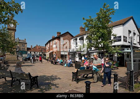 People relaxing in the sunshine Market Square Thirsk North Yorkshire England UK United Kingdom GB Great Britain - Stock Image