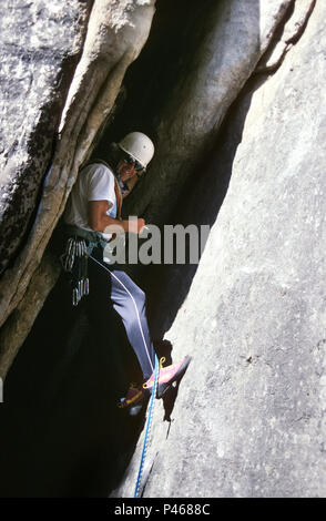 A rock climber takes a cigarette break wedged in a crack - Stock Image
