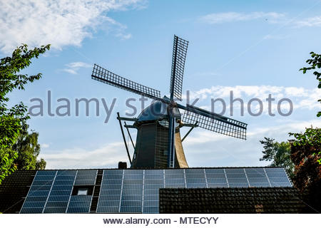 Traditional windmill juxtaposed with photovoltaic solar panels in Ramsloh, Saterland, Lower Saxony, northern Germany. - Stock Image