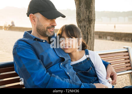 Father and daughter sitting on a bench on the waterfront having a good conversation in a sunny day - Stock Image