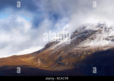 A snow and cloud covered summit of Slioch above Loch Maree in the Scottish Highlands, Scotland, UK. - Stock Image