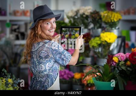 Female florist taking photograph of flowers from digital tablet in flower shop - Stock Image